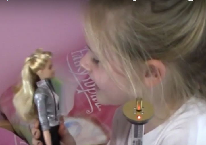 Little girl talking to doll